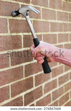 Man hitting an exterior face brick wall with a metal claw hammer in a conceptual image, close up of his hand - stock photo