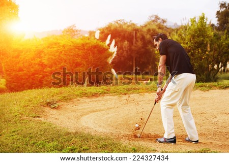 Man hitting golf ball from sand trap at sunny evening, rich adult man playing golf, strong golf shot in action,wealthy man at recreation playing golf on green course,golfer hitting ball in action - stock photo