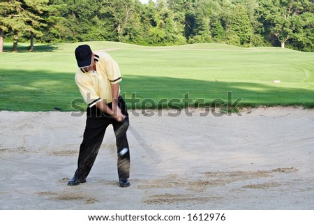 Man hitting out of sand trap.  Sand flying and ball visible in front of pant leg. - stock photo
