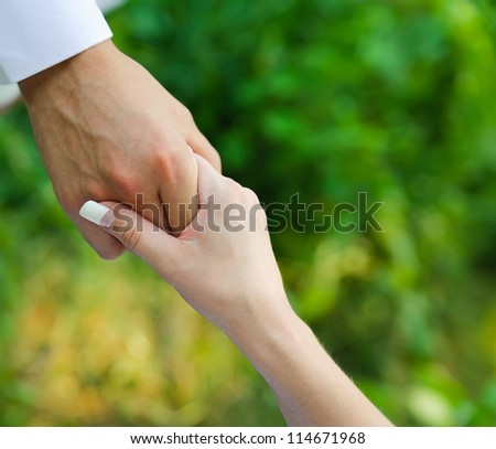 man hold a woman fingers by the hand. male assistance. Blur nature background