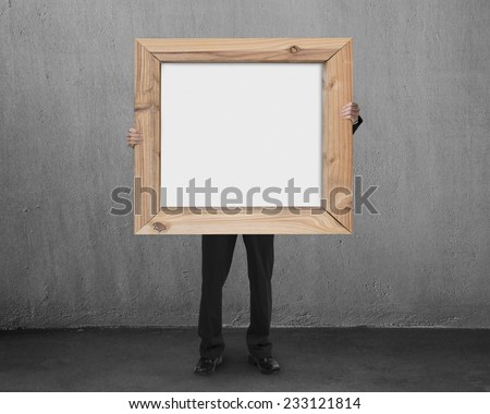 man hold blank whiteboard with wooden frame in gray concrete room background - stock photo