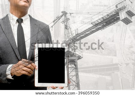 man hold computer tablet double exposure with construction crane - stock photo