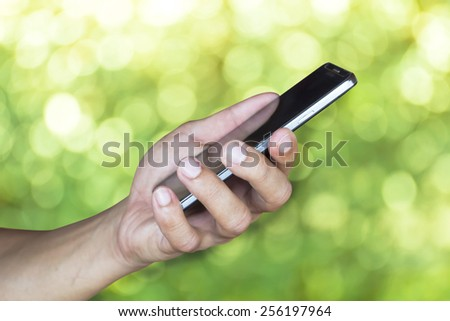 Man hold mobile smart phone green background  - stock photo