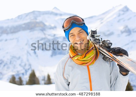 man hold ski in beautiful Alpine landscape. Blue sky in winter on background, skier at the mountains