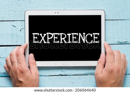 """Man hold tablet pc with text """"experience"""" over blue table - stock photo"""