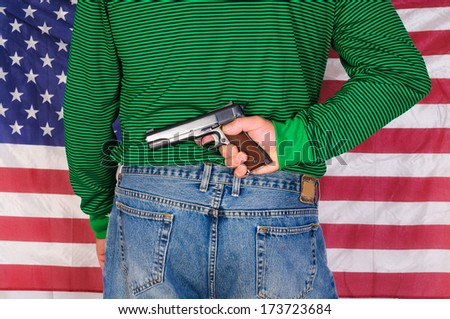 Man holding a 1911, 45 ACP behind his back in front of an American flag - stock photo