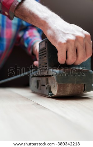 Man holding a belt sander on table sanding surface - stock photo