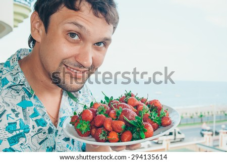 man holding a big bowl of berries and smiling - stock photo