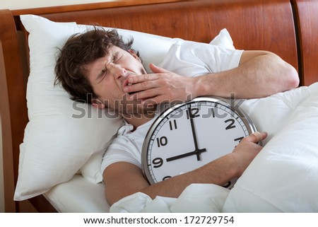 Man holding a big clock and waking up - stock photo