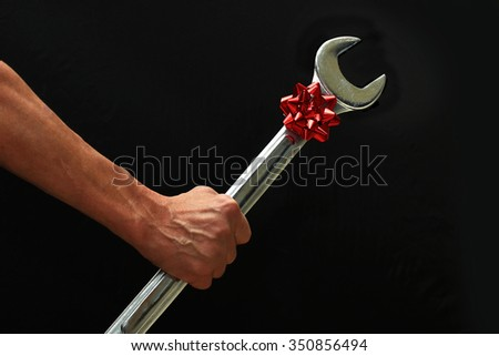Man Holding a Big Wrench with a Christmas Bow on it.  - stock photo