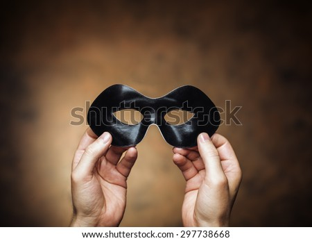 Man holding a black eye mask in his hands. - stock photo