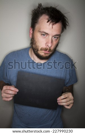 Man holding a blank sign not looking very awake - stock photo