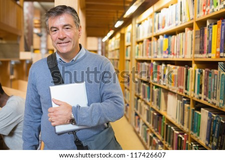 Man holding a book to his chest in a library
