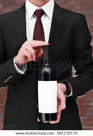 Man holding a bottle of red wine in hands on brick wall background