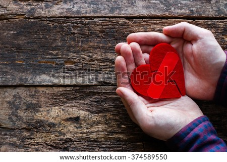man holding a broken heart glued on a wooden background - stock photo
