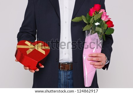 Man holding a bunch of flowers and a heart shaped box of chocolates.