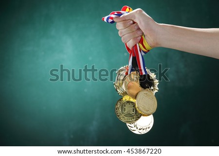 man holding a bunch of  medals in front of blackboard