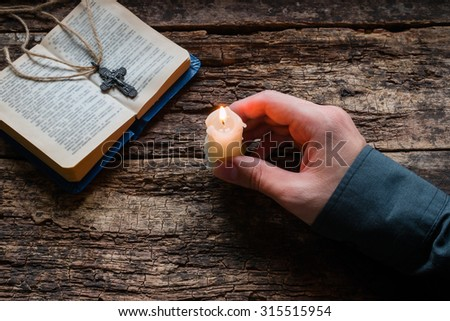 man holding a candle in front of the bible and cross selective focus - stock photo