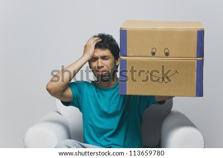 Man holding a cardboard box and looking sad - stock photo