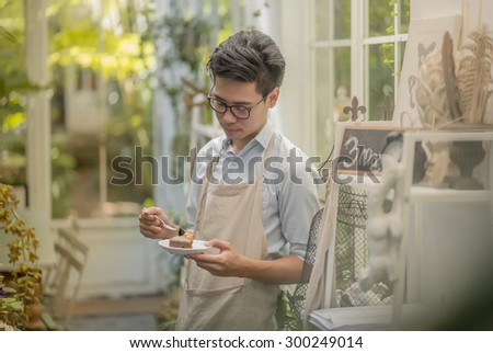 man holding a chocolate cake in vintage room - stock photo