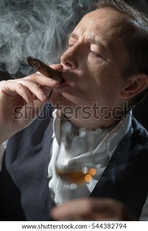 Man holding a cigar in his mouth