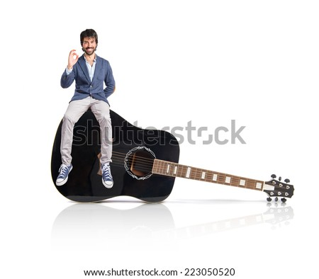 Man holding a clock sitting on guitar - stock photo