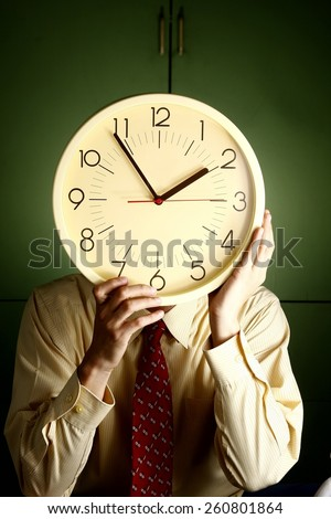 Man holding a clock to his face Photo of a man in a business suit holding a clock to his face - stock photo