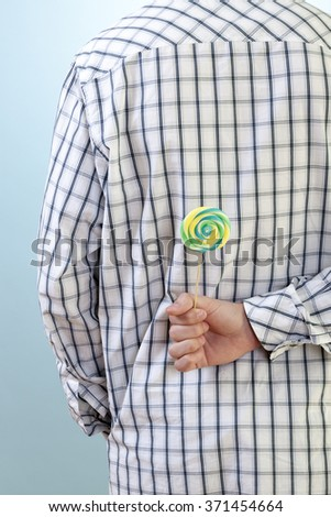 Man holding a colorful sugar candy indicating he is cheating on his diet or trying to trick his girlfriend. - stock photo