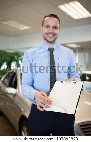 Man holding a contract in a dealership - stock photo