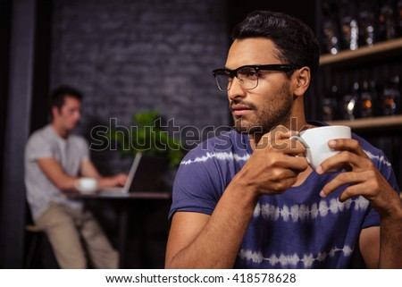Man holding a cup of coffee in a coffee shop - stock photo