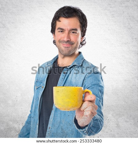 Man holding a cup of coffee over textured background - stock photo