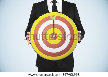 Man holding a dart board with a direct hit on target - stock photo