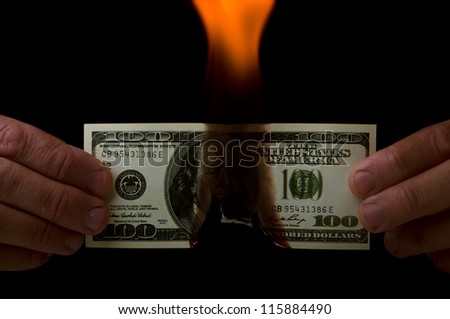 man holding a dollar in flame on black background - stock photo