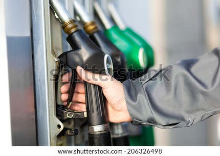 Man holding a fuel nozzle - stock photo