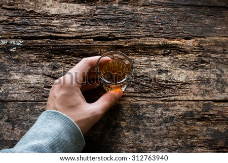 man holding a glass of alcohol on a wooden background - stock photo
