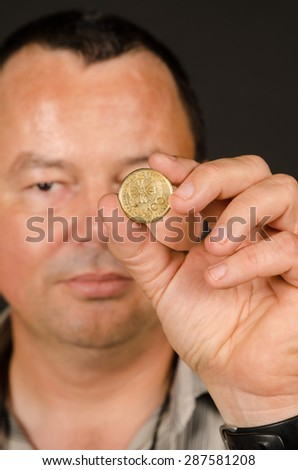 Man holding a 100 Greek drachma coin - stock photo