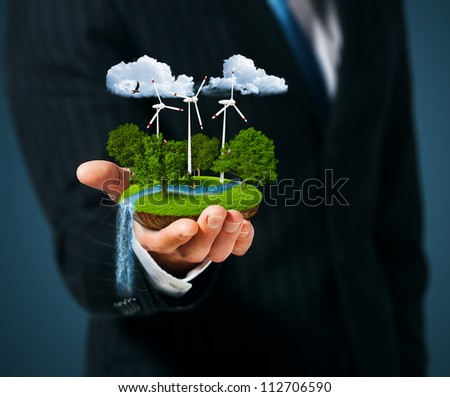 Man holding a green meadow with Wind turbines