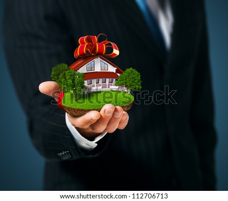 Man holding a ground with House in  hand. Gift