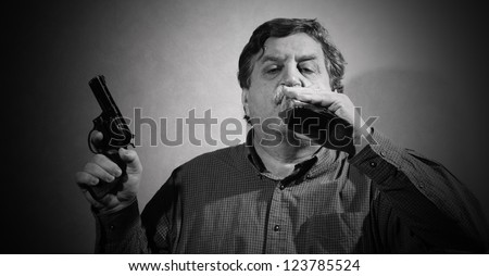 man holding a gun in his hand and drank from a bottle of whiskey - stock photo