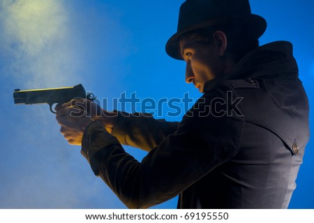Man holding a gun, shooted in studio on a blue background with yellow light and smoke