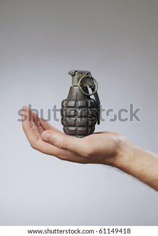 Man holding a hand grenade in his hand - stock photo