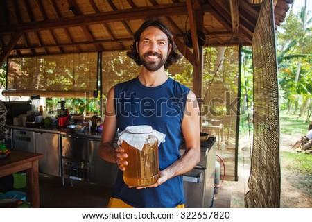 Man holding a jar of honey (or kombucha tea) - stock photo