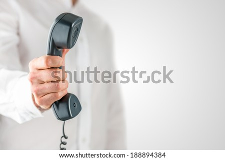 Man holding a landline telephone receiver or handset in his hand with a dangling cord, close up view of the instrument against his white shirt. - stock photo