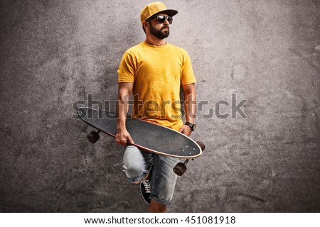 Man holding a longboard and leaning against a rusty concrete wall