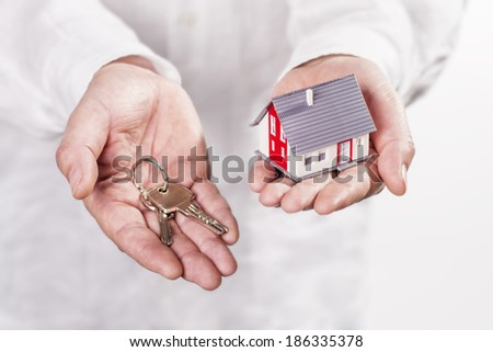 Man holding a model house in one hand and a key in the other hand