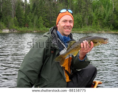man holding a northern pike he caught - stock photo