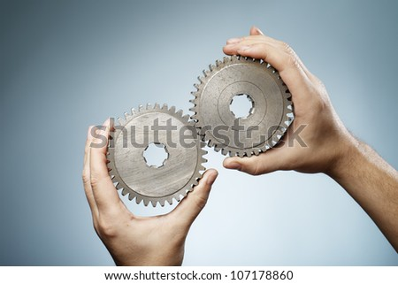 Man holding a pair of old metallic cog gear wheels in his hands. - stock photo