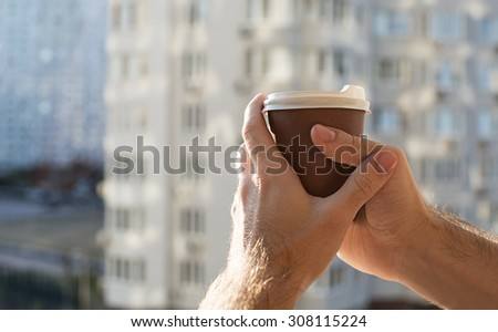 man holding a paper coffee cup - stock photo