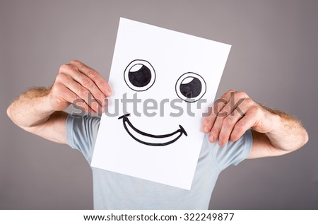 Man holding a paper with a face having a joy expression
