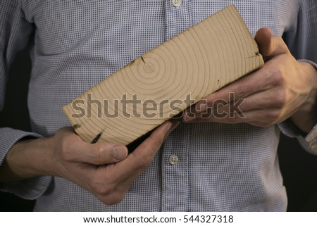 man holding a piece of wood or trunk as an expression of aging or environmental protection.